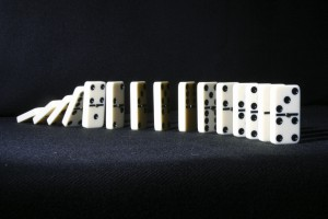Dominoes falling from back on black background
