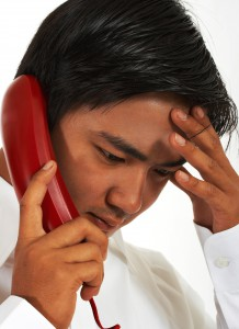 Busy Worker On The Telephone Looking Stressed And Serious